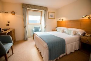 A bed or beds in a room at Moorings Hotel