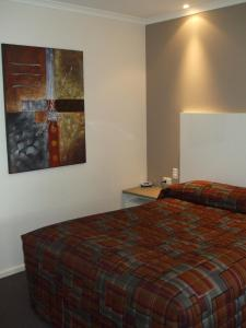 A bed or beds in a room at McLaren Vale Motel & Apartments