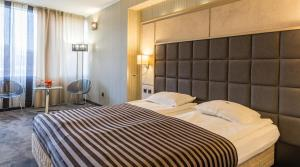 A bed or beds in a room at Cosmopolitan Hotel & Wellness