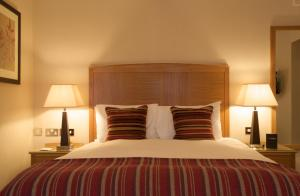 A bed or beds in a room at The Thames Riviera Hotel