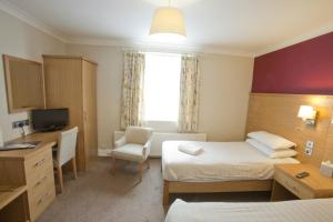 A bed or beds in a room at Wheatlands Lodge Hotel