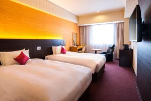 A bed or beds in a room at Chisun Grand Nagano