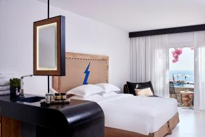 A bed or beds in a room at Royal Myconian - Leading Hotels of the World