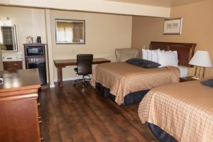 A bed or beds in a room at Abram Inn & Suites