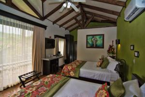 A bed or beds in a room at Hotel Arenal Springs Resort & Spa