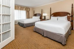 A bed or beds in a room at Richmond Inn & Suites Trademark Collection by Wyndham