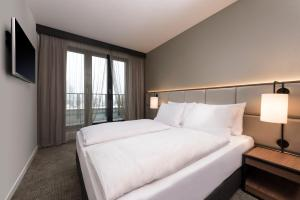 A bed or beds in a room at Adina Apartment Hotel Frankfurt Westend