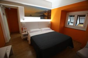 A bed or beds in a room at Hotel Fiume