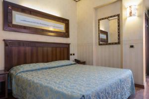 A bed or beds in a room at Duca D'Aosta Hotel