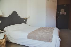A bed or beds in a room at Hôtel Logis Le Bourbon