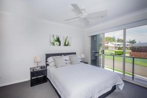 A bed or beds in a room at Escape At Nobbys Executive Townhouse 1 74 Pacific Drive
