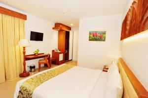 A bed or beds in a room at Kautaman Hotel