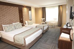A bed or beds in a room at Ankara Gold Hotel