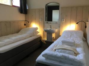 A bed or beds in a room at Resort Bungalows Dellewal