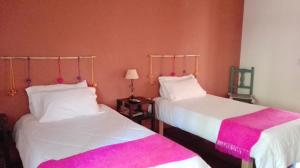 A bed or beds in a room at Pumahuasi Hostal Boutique