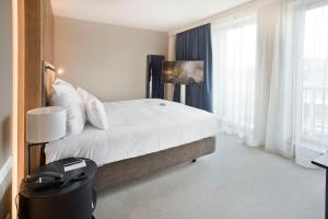 A bed or beds in a room at Pestana Amsterdam Riverside