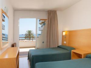 A bed or beds in a room at Apartamentos Mar y Playa