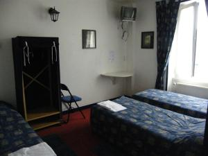 A bed or beds in a room at Hôtel de la Gare