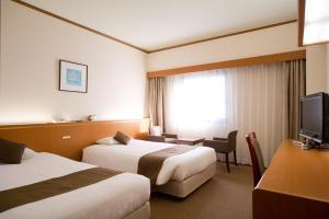 A bed or beds in a room at Daiichi Inn Ikebukuro