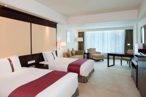 سرير أو أسرّة في غرفة في نزل هوليداي شيفو قوانغتشو