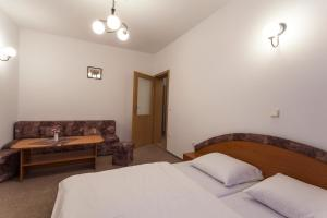 A bed or beds in a room at Hotel Adršpach Garni