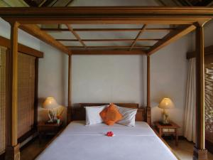 A bed or beds in a room at Puri Bagus Manggis
