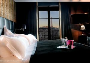 A bed or beds in a room at First Hotel Paris Tour Eiffel
