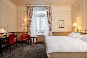 A bed or beds in a room at Small Luxury Hotel Ambassador Zurich