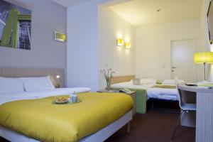 Un ou plusieurs lits dans un hébergement de l'établissement Aparthotel Adagio Access Bruxelles Europe Aparthotel