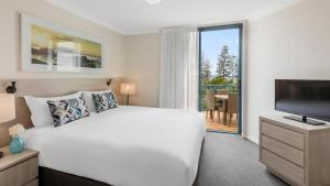 A bed or beds in a room at Oaks Gold Coast Calypso Plaza Suites