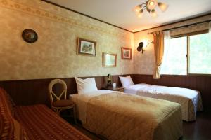 A bed or beds in a room at Piccolo Hotel Opera Karuizawa