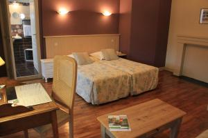 A bed or beds in a room at Hotel L'Amphitryon