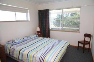 A bed or beds in a room at Oceanview, 6 Stewart Street