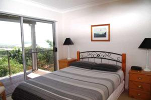 A bed or beds in a room at Coastwatch, 26 Comara Terrace