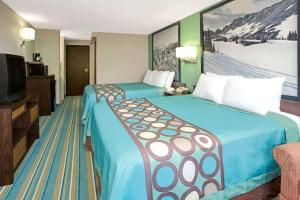 A bed or beds in a room at Super 8 by Wyndham Denver Stapleton