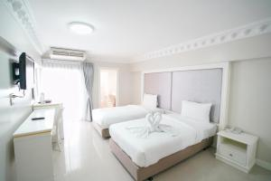 A bed or beds in a room at Romance Hotel Sukhumvit 97