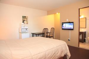 A bed or beds in a room at Motel Grande Ile