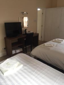 A bed or beds in a room at Green Gables Hotel