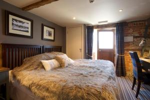 A bed or beds in a room at The Woolpack Inn