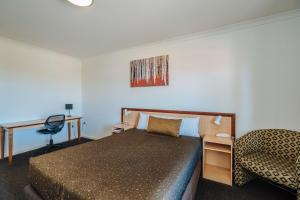 A bed or beds in a room at Canning Bridge Auto Lodge