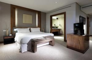 A bed or beds in a room at Eurostars Suites Mirasierra