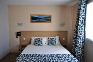 A bed or beds in a room at Brit Hotel Azur