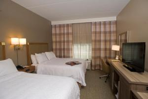 A bed or beds in a room at Hampton Inn Springfield-Southeast, MO