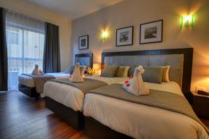 Ένα ή περισσότερα κρεβάτια σε δωμάτιο στο St. Julian's Bay Hotel