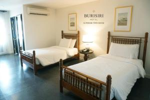 A bed or beds in a room at Buri Siri Boutique Hotel
