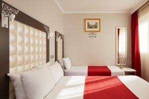 A bed or beds in a room at Grand Hôtel Amelot
