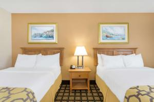 A bed or beds in a room at Baymont by Wyndham Kitty Hawk Outer Banks