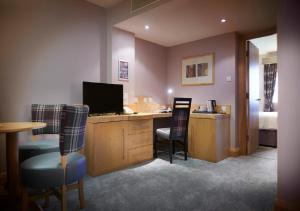 A television and/or entertainment center at The Suites Hotel & Spa Knowsley - Liverpool by Compass Hospitality