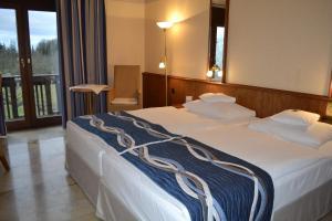 Ein Bett oder Betten in einem Zimmer der Unterkunft Flair Park Hotel Ilshofen