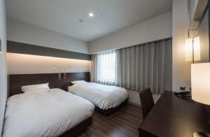 A bed or beds in a room at Nagoya Kanayama Hotel